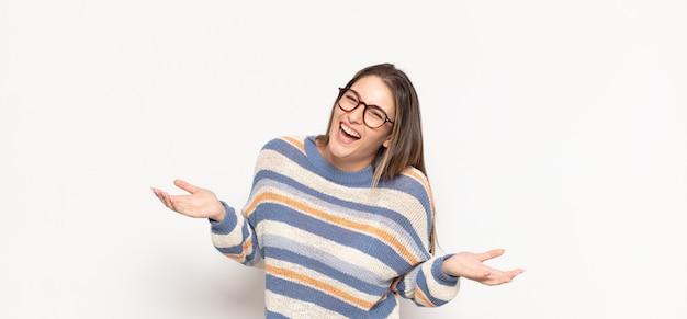 Jonge blonde vrouw die buitengewoon blij en verrast kijkt, succes viert, schreeuwt en springt
