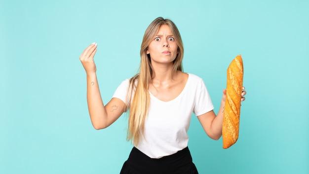 Jonge blonde vrouw die capice of geldgebaar maakt, zegt dat je moet betalen en een stokbrood vasthoudt