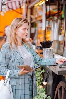 Jonge blonde vrouw die contactloos betaalt met creditcard in straatcafé