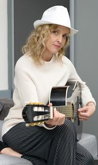 Jonge blonde vrouw die de akoestische gitaar speelt