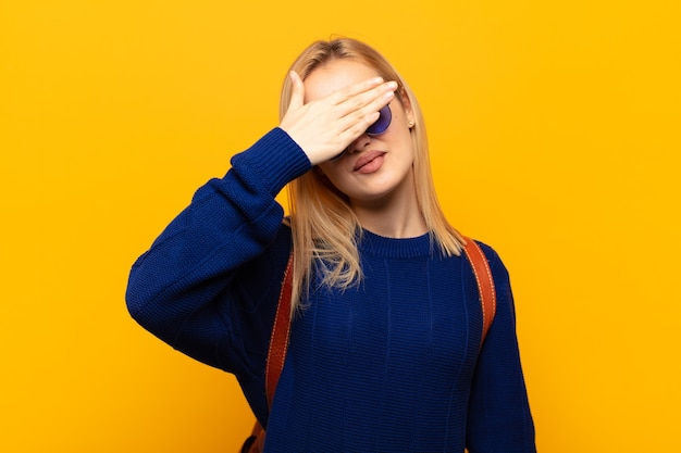 Jonge blonde vrouw die de ogen bedekt met één hand, bang of angstig voelt, zich afvraagt of blindelings wacht op een verrassing
