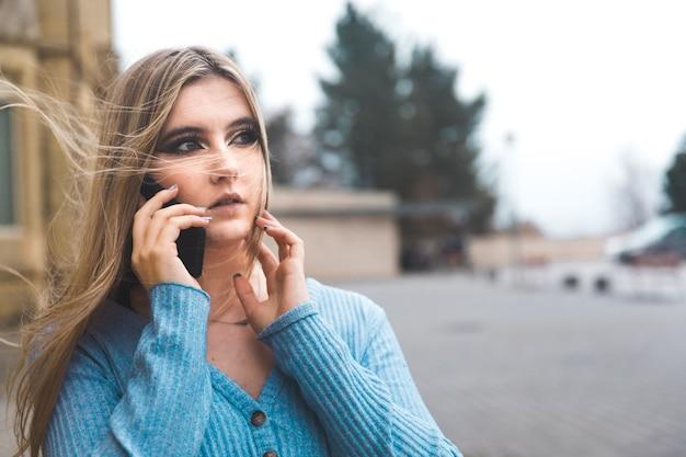 Jonge blonde vrouw die door de mobiele telefoon in de straat neemt