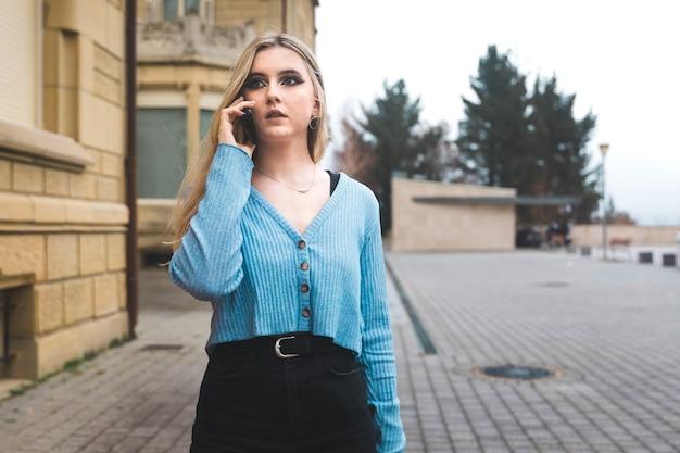 Jonge blonde vrouw die door mobiele telefoon op straat neemt