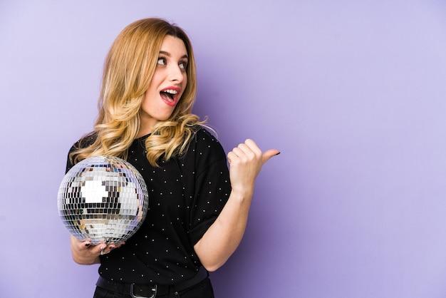 Jonge blonde vrouw die een bal van de nachtpartij houdt geïsoleerde punten met duimvinger weg, lachend en zorgeloos.