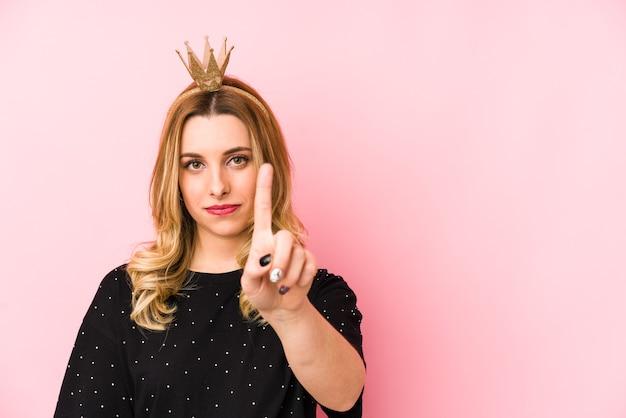 Jonge blonde vrouw die een geïsoleerde kroon draagt die nummer één met vinger toont.