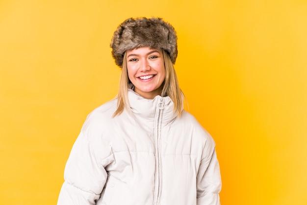 Jonge blonde vrouw die een geïsoleerde winterkleren draagt jonge blonde vrouw die op gele ruimte wordt geïsoleerd gelukkig, glimlachend en vrolijk <mixto>