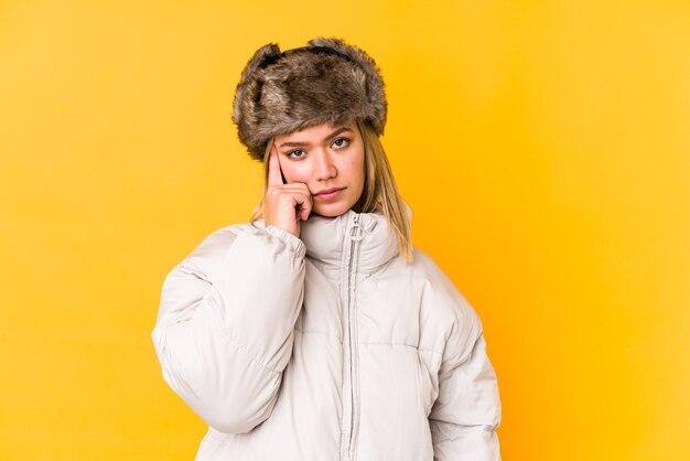 Jonge blonde vrouw die een geïsoleerde winterkleren draagt jonge blonde vrouw die tempel met vinger richt, denkt, gericht op een taak