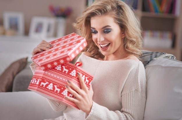 Jonge blonde vrouw die een gift van kerstmis opent