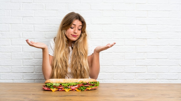 Jonge blonde vrouw die een grote sandwich houdt die twijfels heeft