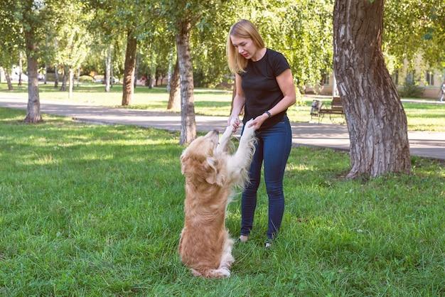 Jonge blonde vrouw die een hond vasthoudt bij de voorpoten. hondenras retriever met spelen met een meisje in het park