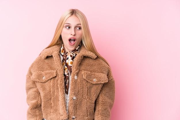 Jonge blonde vrouw die een jas draagt tegen een roze muur die wordt geschokt vanwege iets dat ze heeft gezien.