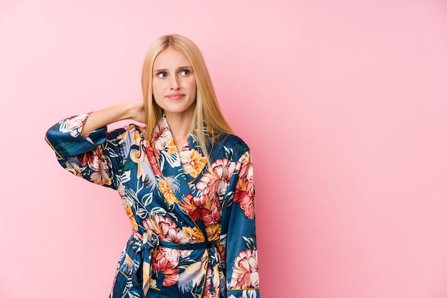 Jonge blonde vrouw die een kimonopyjama draagt die het achterhoofd aanraakt, denkt en een keuze maakt.