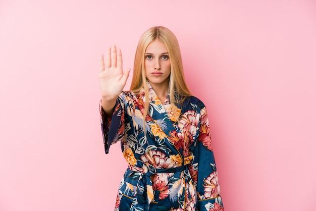 Jonge blonde vrouw die een kimonopyjama draagt die zich met uitgestrekte hand bevindt die eindeteken toont