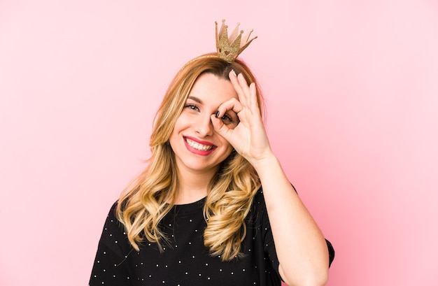 Jonge blonde vrouw die een kroon draagt geïsoleerd opgewonden houdend ok gebaar op oog.