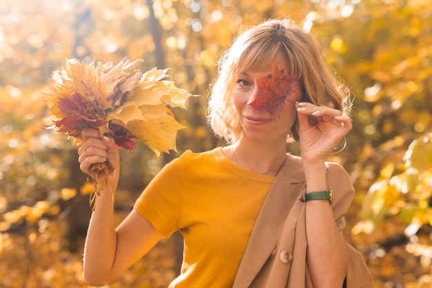 Jonge blonde vrouw die één oog bedekt met rood esdoornblad. herfst en seizoen concept. buiten vallen vrouwelijk portret close-up met gebladerte
