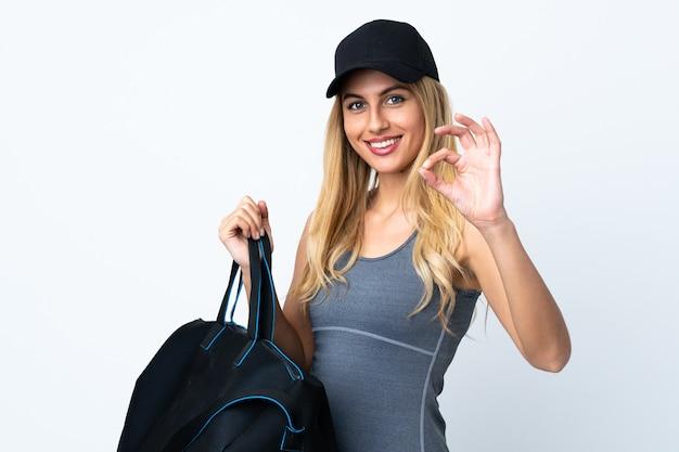 Jonge blonde vrouw die een sporttas houdt over geïsoleerde witte muur die ok teken met vingers toont