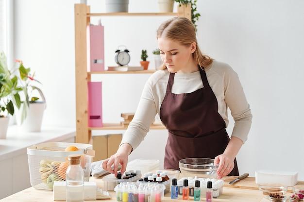 Jonge blonde vrouw die een van de flessen met etherische oliën neemt tijdens het kiezen van geur voor handgemaakte zeep