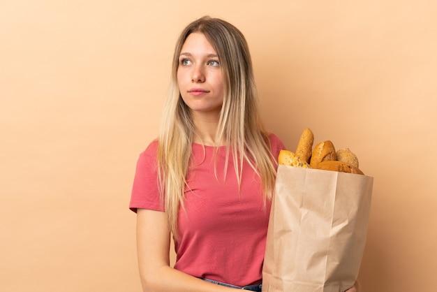 Jonge blonde vrouw die een zak vol brood houdt dat op beige muur wordt geïsoleerd die kant kijkt