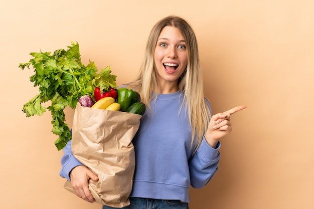 Jonge blonde vrouw die een zakhoogtepunt houdt van groenten die vinger aan de kant richten