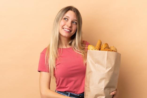 Jonge blonde vrouw die een zakhoogtepunt van brood houdt dat op beige en muur wordt geïsoleerd die omhoog lacht kijkt