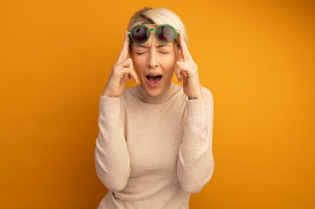 Jonge blonde vrouw die een zonnebril draagt en ze opvoedt met gesloten ogen en open mond