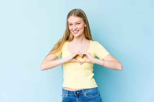 Jonge blonde vrouw die en een hartvorm met handen glimlacht toont.