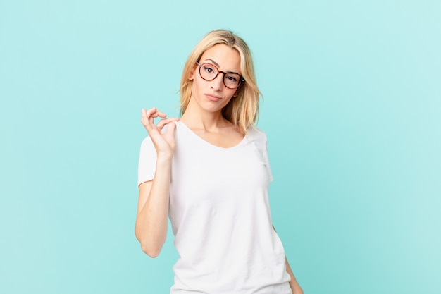 Jonge blonde vrouw die er arrogant, succesvol, positief en trots uitziet