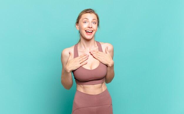 Jonge blonde vrouw die er blij, verrast, trots en opgewonden uitziet, wijzend naar zichzelf. sport concept