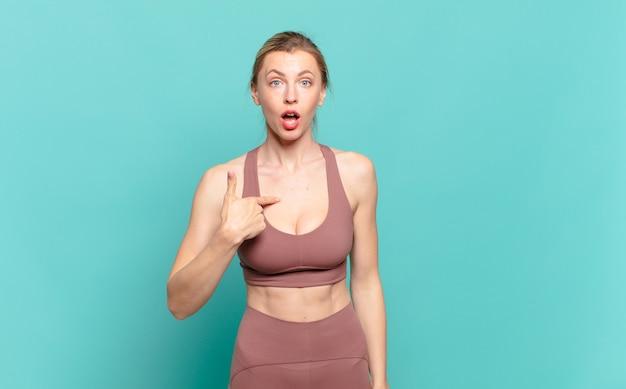 Jonge blonde vrouw die er gelukkig, trots en verrast uitziet, vrolijk naar zichzelf wijst, zelfverzekerd en verheven. sport concept