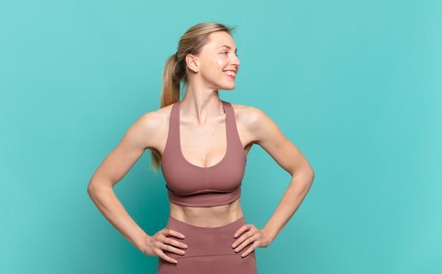 Jonge blonde vrouw die er gelukkig, vrolijk en zelfverzekerd uitziet, trots lacht en opzij kijkt met beide handen op de heupen. sport concept