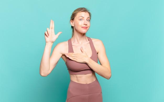Jonge blonde vrouw die er gelukkig, zelfverzekerd en betrouwbaar uitziet, glimlacht en een overwinningsteken toont, met een positieve houding. sport concept