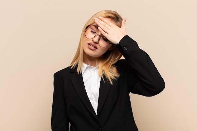 Jonge blonde vrouw die er gestrest, moe en gefrustreerd uitziet, het zweet van het voorhoofd droogt, zich hopeloos en uitgeput voelt