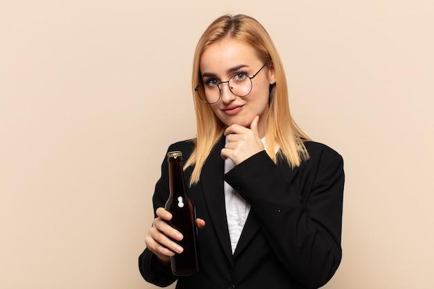 Jonge blonde vrouw die er serieus, verward, onzeker en attent uitziet, twijfelend tussen opties of keuzes
