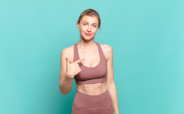 Jonge blonde vrouw die er trots, zelfverzekerd en gelukkig uitziet, glimlacht en naar zichzelf wijst of nummer één teken maakt. sport concept