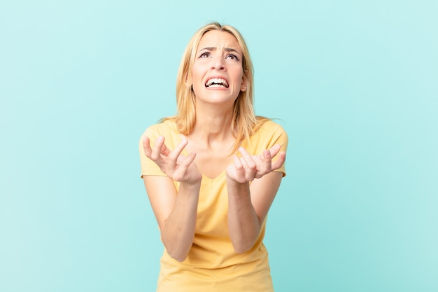 Jonge blonde vrouw die er wanhopig, gefrustreerd en gestrest uitziet