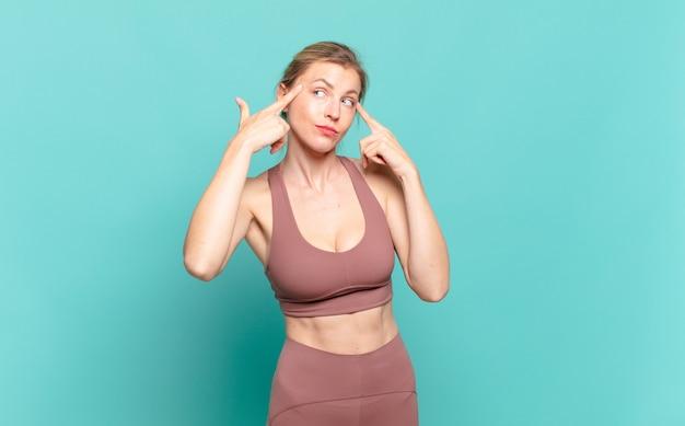 Jonge blonde vrouw die geconcentreerd kijkt en hard nadenkt over een idee, een oplossing voor een uitdaging of probleem verbeeldt. sport concept