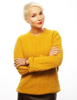 Jonge blonde vrouw die gele sweater draagt die op wit wordt geïsoleerd