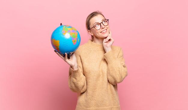 Jonge blonde vrouw die gelukkig lacht en dagdroomt of twijfelt, opzij kijkend. wereld concept