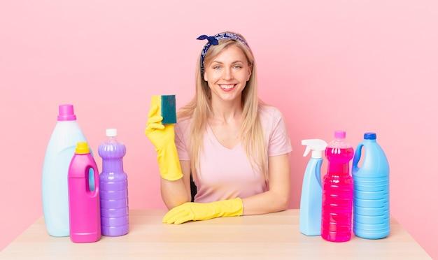 Jonge blonde vrouw die gelukkig lacht met een hand op de heup en zelfverzekerd. huishoudster concept