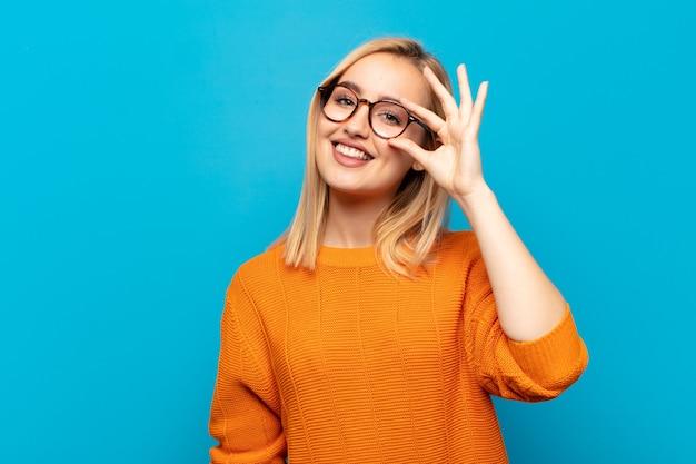 Jonge blonde vrouw die gelukkig met grappig gezicht glimlacht, een grapje maakt en door kijkgaatje kijkt, geheimen bespioneert