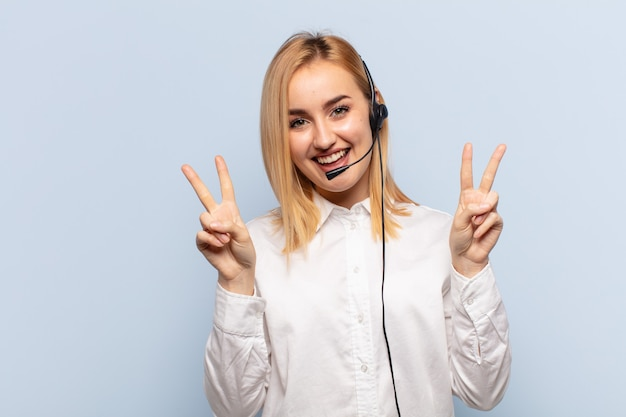 Jonge blonde vrouw die gelukkig, vriendelijk en tevreden glimlacht en kijkt, overwinning of vrede met beide handen gebaart