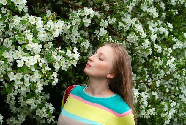Jonge blonde vrouw die geniet van de geur van appelboombloemen