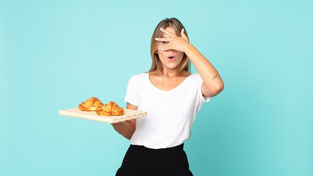 Jonge blonde vrouw die geschokt, bang of doodsbang kijkt, haar gezicht bedekt met de hand en een croissantblad vasthoudt