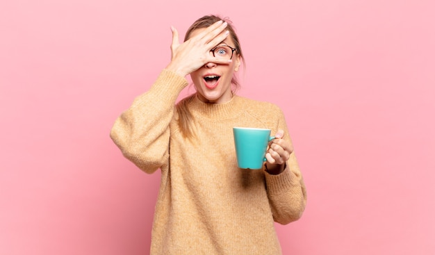 Jonge blonde vrouw die geschokt, bang of doodsbang kijkt, haar gezicht bedekt met de hand en tussen de vingers gluurt. koffie concept