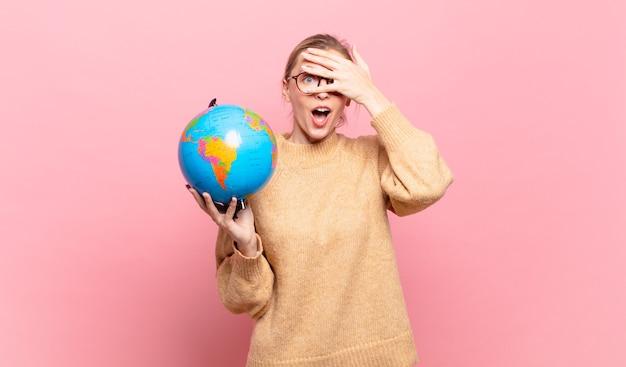 Jonge blonde vrouw die geschokt, bang of doodsbang kijkt, haar gezicht bedekt met de hand en tussen de vingers gluurt. wereld concept