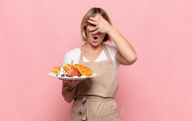 Jonge blonde vrouw die geschokt, bang of doodsbang kijkt, haar gezicht bedekt met de hand en tussen de vingers gluurt