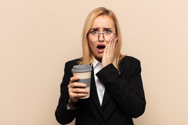 Jonge blonde vrouw die geschokt en bang voelt, doodsbang kijkt met open mond en handen op de wangen