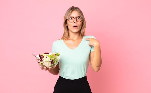 Jonge blonde vrouw die geschokt en verrast kijkt met de mond wijd open, naar zichzelf wijst en een salade vasthoudt