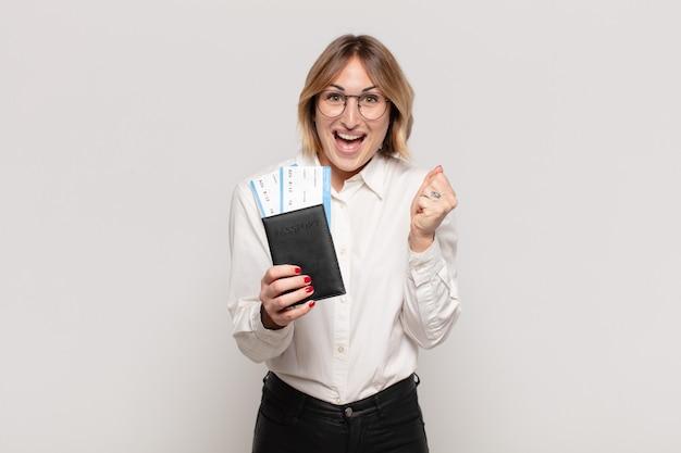 Jonge blonde vrouw die geschokt, opgewonden en gelukkig voelt, lacht en succes viert