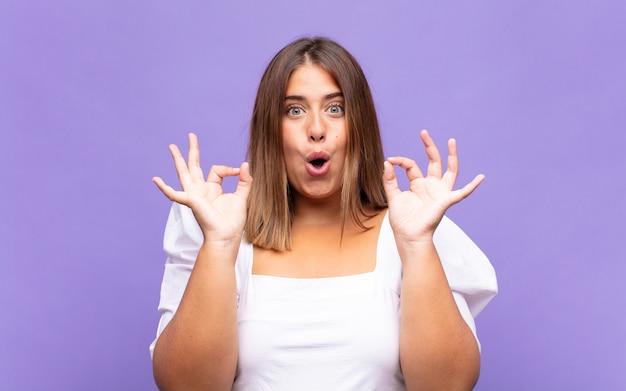 Jonge blonde vrouw die geschokt, verbaasd en verrast voelt, goedkeuring toont en goed teken met beide handen maakt